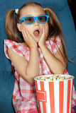 Little girl eating popcorn during a movie Royalty Free Stock Images