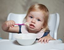 Little girl eating porridge Stock Photo