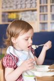 Little girl eating porridge at home Royalty Free Stock Photography
