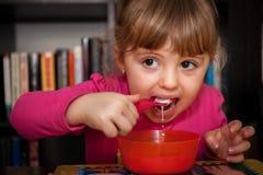 Little girl eating porridge Stock Photography