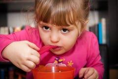 Little girl eating porridge Royalty Free Stock Photo