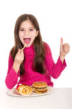 Little girl eating potatoes. Thumb up Royalty Free Stock Photo