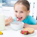 Little girl eating. Pretty little girl eating cereal and strawberries in the white kitchen royalty free stock photography