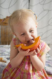 Little girl eating a pumpkin. With a funny face Royalty Free Stock Images