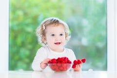 Little girl eating raspberry in white dining room. Beautiful little girl eating raspberry in a white dining room Stock Image