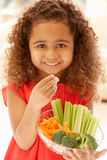 Little girl eating raw vegetables stock photos