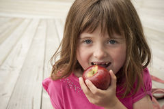 Little girl eating red apple Royalty Free Stock Photo