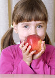 Little girl eating red apple. Stock Image