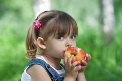 Little girl eating red apple outdoor stock photos
