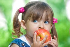 Little girl eating red apple outdoor summertime stock photography