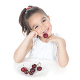 Little girl eating red berries Stock Photos
