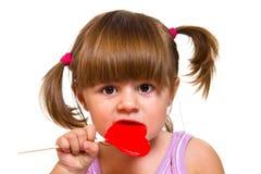 Little girl eating red heart lollipop Stock Photo