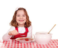 Little girl eating red tomato soup Stock Photography