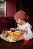 Little girl eating in restaurant Stock Photo
