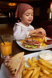 Little girl eating in restaurant Royalty Free Stock Photography