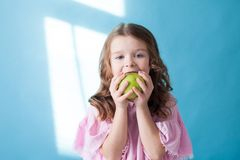 Little girl eating ripe Green Apple healthy food royalty free stock photo