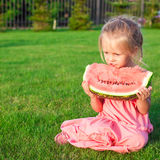 Little girl eating a ripe juicy watermelon in Royalty Free Stock Photography