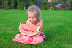 Little girl eating a ripe juicy watermelon in Royalty Free Stock Images