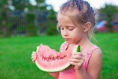 Little girl eating a ripe juicy watermelon in Stock Images