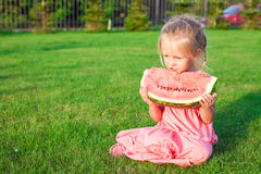 Little girl eating a ripe juicy watermelon in Stock Photography