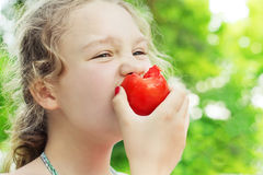 Little girl is eating ripe tomato Stock Photography