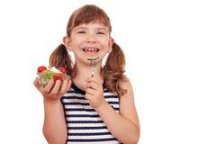 Little girl eating salad Stock Image
