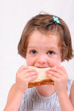 Little girl eating sandwich. Little girl eating a sandwich, isolated over white stock images