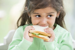 Little girl eating sandwich at home Royalty Free Stock Photo