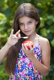 Little girl eating a slice of tomato. Portrait of a beautiful Little girl eating a slice of tomato on the background of summer park Royalty Free Stock Image