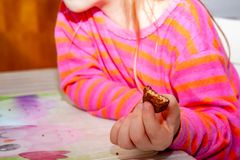 Little girl eating Snickers chocolate bar for breakfast royalty free stock photography