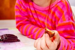 Little girl eating Snickers chocolate bar for breakfast royalty free stock images