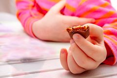 Little girl eating Snickers chocolate bar for breakfast stock images