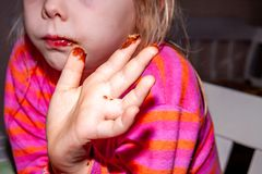 Little girl eating Snickers chocolate bar for breakfast stock image