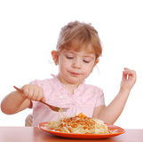 Little girl eating spaghetti stock photos