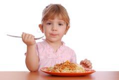 Little girl eating spaghetti Stock Images