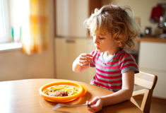 Little girl eating spaghetti Stock Image