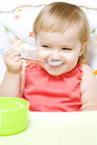 Little girl eating with spoon Stock Photos