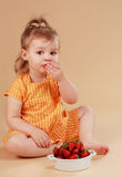 Little girl eating strawberries Stock Photo