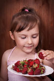 Little girl eating strawberries Royalty Free Stock Image