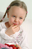 Little girl eating strawberry Stock Photos