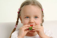 Little girl eating strawberry Royalty Free Stock Images