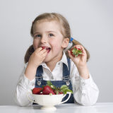 Little girl eating strawberry Royalty Free Stock Photography