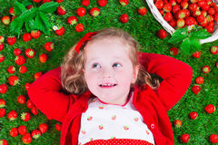 Little girl eating strawberry Stock Image