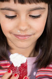Little girl eating strawberry with cream Royalty Free Stock Photography