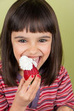 Little girl eating strawberry with cream Royalty Free Stock Photo