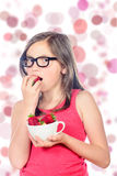 A little girl eating a strawberry Royalty Free Stock Photos