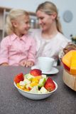 Little girl eating strawberry with her mother Stock Photo