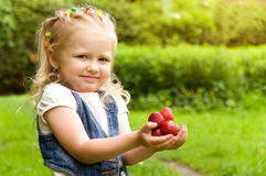 Little girl eating a strawberry in nature Royalty Free Stock Photos