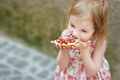 Little girl eating a strawberry tart Stock Photography