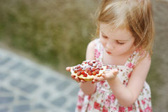 Little girl eating a strawberry tart Stock Photos